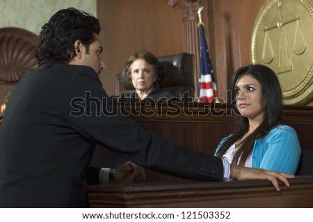 Advocate with witness and judge sitting in the background - stock photo