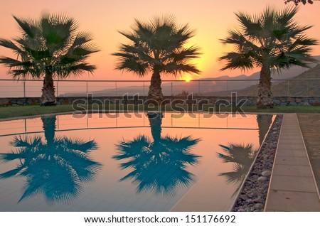 Aegean Sunrise - Summer sunrise over the Cretan mountains with palm trees reflecting in a pool in Malia, Crete - stock photo