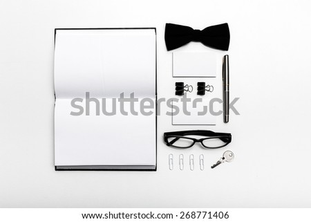 Aerial. Business objects in order on white desk. /Overhead of essentials office objects in black and white. - stock photo