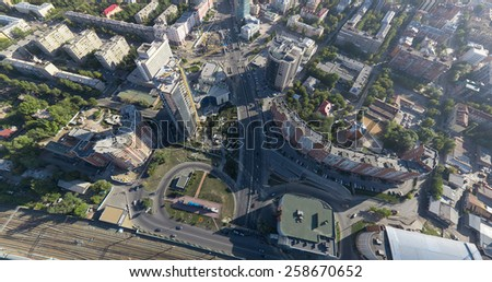 Aerial city view with crossroads and roads, houses and buildings, green parks - stock photo