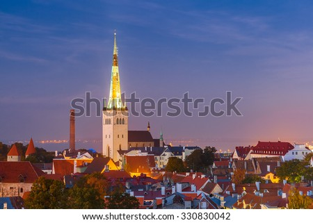 Aerial cityscape with Medieval Old Town and St. Olaf Baptist Church in Tallinn at autumn night, Estonia - stock photo