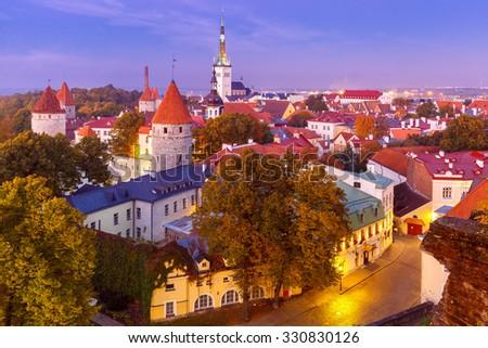 Aerial cityscape with Medieval Old Town, St. Olaf Baptist Church and Tallinn City Wall illuminated in autumn twilight, Tallinn, Estonia - stock photo