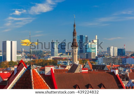 Aerial cityscape with old town hall spire, roofs, golden weather vane and modern office buildings skyscrapers in the background in Tallinn in the day, Estonia - stock photo