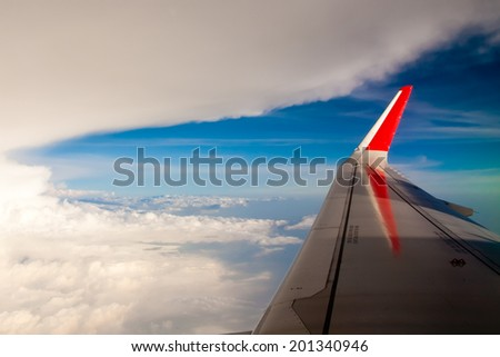 Aerial cloudscape from the airplane board with the mainplane - stock photo