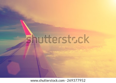 Aerial cloudscape from the airplane board with the mainplane - instagram style - stock photo