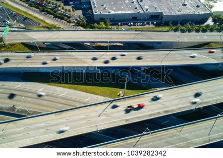 Aerial drone photo of fast cars in motion on a highway interchange
