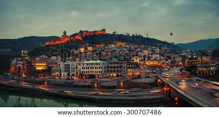 Aerial evening view of Old Tbilisi, Georgia with illuminated castle at the background - stock photo
