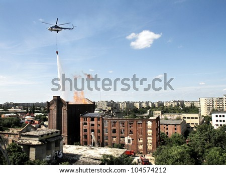 Aerial firefighting - helicopter used to fight fire from a burning building - stock photo