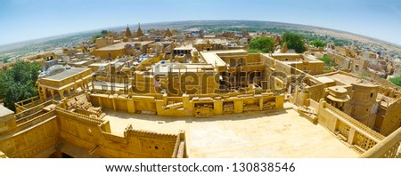Aerial fish-eye panoramic view over Jaisalmer rooftops and surrounding desert from Royal Palace top, Rajasthan, India - stock photo