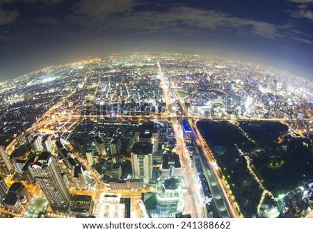 Aerial fisheye view of buildings in Osaka in Japan at night - stock photo