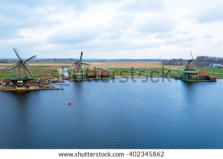 Aerial from traditional windmills in a typical dutch landscape at Zaanse Schans in the Netherlands - stock photo