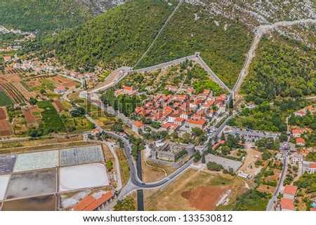 Aerial helicopter photo of medieval town Ston, famous second world largest stone wall and saltern, Peljesac peninsula near Dubrovnik, Croatia. - stock photo
