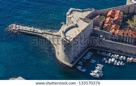 Aerial helicopter shoot of Dubrovnik old town harbor and st. John fortress. - stock photo
