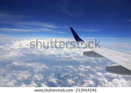 Aerial high in the sky shot from above the clouds with the wing of a commercial jet plane that turns upwards on the left side with the United States of America below. - stock photo