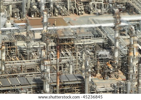 Aerial image of oil refinery featuring blurred fumes from stack. - stock photo