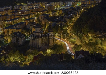 Aerial night city view of downtown residential Racadau district with church, at the foot of Tampa mountain in Brasov city, Romania. - stock photo