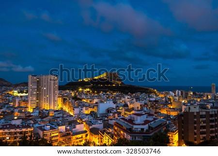 Aerial night view of Alicante, Costa Blanca, Spain. Old city center with harbor, illumination. Santa Barbara Castle located on Mount Benacantil - stock photo
