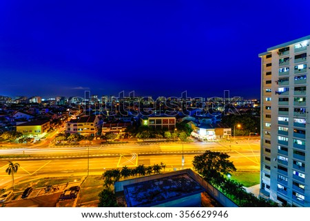 Aerial night view of new estate, HDB housing complex near the highway in Eunos area, Singapore. Blue hour view. Urban motion concept. - stock photo