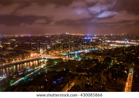 Aerial Night view of Paris City and Seine river.he blue light is projected from the top of the Eiffel tower
