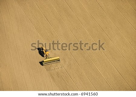 Aerial of farmer tilling crop field in farmland, USA. - stock photo