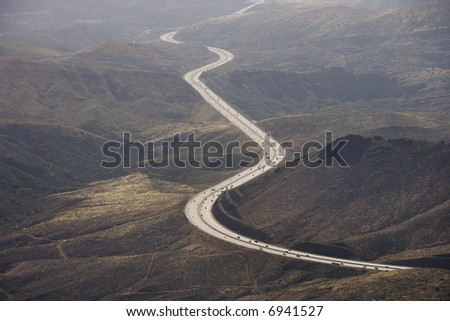 Aerial of Route 14 with traveling vehicles through rural California landscape, USA.