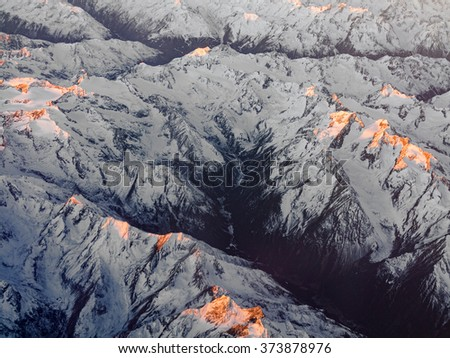 aerial of sunrise in the italian Alps with snow covered mountains