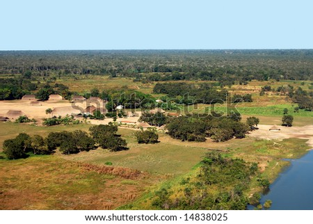 Aerial of traditional Amazon Indian village with houses in circle near Xingu River in Brazil - stock photo
