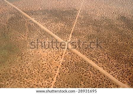 """Aerial of two roads crossing in the desert, making an """"X"""" - stock photo"""