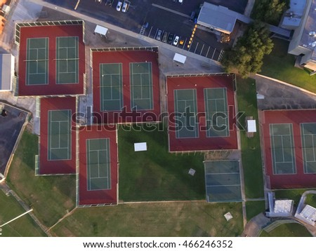 Aerial outdoor tennis court in an athletic complex at Houston, Texas, USA at sunset. Available are baseball fields and parking lots. Urban community athletics program and recreation concept.