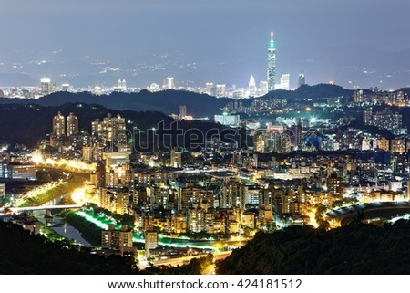 Aerial panorama of overpopulated suburban communities in Taipei at dusk with view of Taipei 101 Tower in downtown & bridges over Xindian River ~ A romantic evening of Taipei in beautiful blue twilight - stock photo