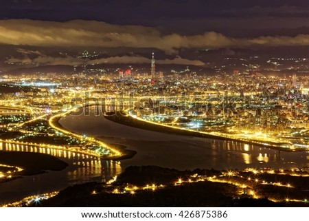 Aerial panorama of Taipei City in a misty gloomy night, with view of Kuandu plain, Tamsui River and downtown area with Taipei 101 Tower among high rise buildings  in XinYi District in evening twilight - stock photo