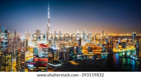Aerial panoramic view of a big futuristic city by night. Business bay, Dubai, United Arab Emirates. Nighttime skyline.  - stock photo