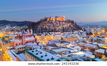 Aerial panoramic view of Ljubljana decorated for Christmas holidays. Roofs covered in snow in winter time. Slovenia, Europe. - stock photo