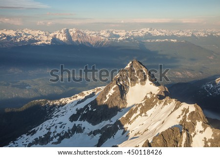 Aerial Picture of a Beautiful Mountain Peak near Squamish, BC, Canada. Taken during a hazy sunny sunset. - stock photo