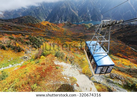 Aerial scenery of a scenic cable car flying over the beautiful autumn valley in the Tateyama Kurobe Alpine Route, Japan ~ Breathtaking view from Daikanbo over magnificent colorful autumn valley - stock photo