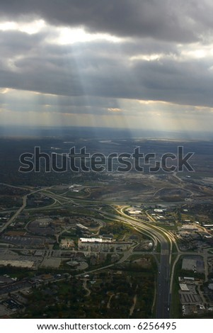 Aerial Shot from the Airplane with Sunrays coming through the clouds - stock photo