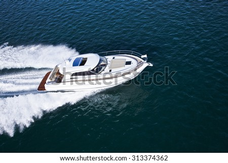 Aerial shot of a beautiful white motor boat with brown details sailing across the sea - stock photo
