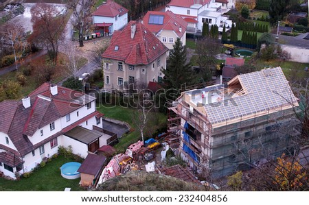 Aerial shot of a new house being built in in a suburban historic neighborhood near a waterfall  in autumn - stock photo
