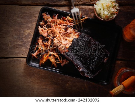 Aerial Shot of Mouth Watering Pulled Pork Dish on Black Serving Tray with Fork. Served on Wooden Table. - stock photo