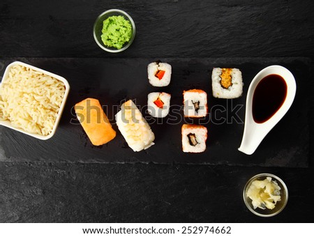 Aerial Shot of Tasty Fresh Sushi Japanese Foods with Sauce on slate plate - stock photo