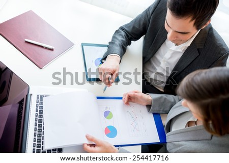 Aerial Shot of Two Business People Reviewing Charts from Business Documents While Sitting at the Worktable. - stock photo