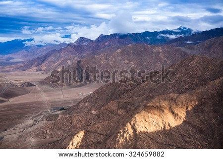 Aerial snowy and rock mountains - stock photo