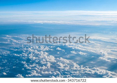 Aerial view above clouds from airplane - stock photo