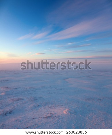 Aerial view above the endless snow covered tundra in time of short winter day. Small hill illuminated the low sun. - stock photo