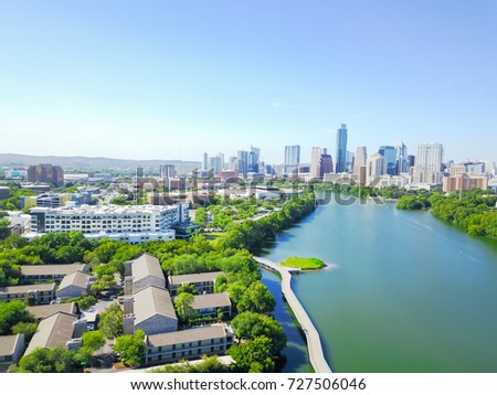 Aerial view Austin state capital of Texas, USA form Lady Bird Lake Creek. Ann and Roy Butler Hike-and-Bike Trail boardwalk along Colorado River and Downtown skyscraper in background. Clean, green city