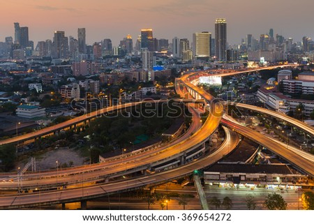 Aerial view city downtown background with highway intersection during twilight - stock photo