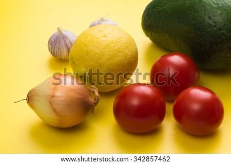 Aerial view closeup guacamole dip ingredients on yellow cutting board.  Top view closeup yellow background, preparation guacamole with avocado tomatoes onion garlic lemon - stock photo