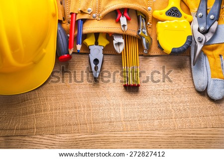 aerial view construction tools  in toolbelt hammer tapeline wrench nippers pliers cutter pencil screwdriver helmet on wooden board  - stock photo