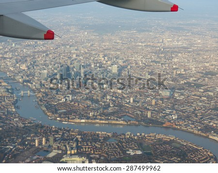 Aerial view from a flying plane in the sky over London city centre - stock photo