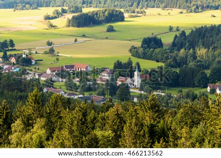 Aerial view from lookout U Jakuba to czech landscape known as Czech Canada. Touristic place. View to forest, field, meadows and small village with rural church in sunny day with blue sky